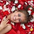 Smiling young girl in rose petal — Stock Photo #2085254