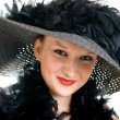 Smiling women in black hat and boa - Stock Photo