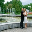 Bride and groom against urban fountain — Stock Photo