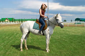 Young girl astride a horse — Stock Photo