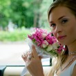 Bride with flowers in car — Stockfoto
