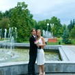 Bride and groom against urban fountain — Stock Photo #2135710
