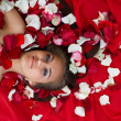 Smiling girl in rose petal — Stock Photo