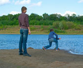 Young men throws stone into the river — Stock Photo