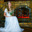 Bride against fireplace — Stock Photo