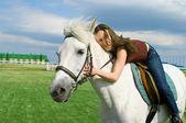 Girl embraces a white horse — Stock Photo
