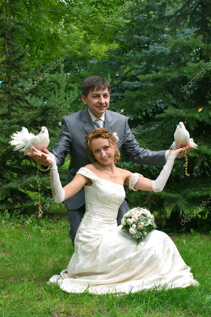 Bride and groom with pigeons against green furtrees  Stock Photo #2156817