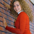 Girl against red brick wall — Stock Photo
