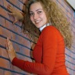 Girl against red brick wall — Stock Photo #2198884