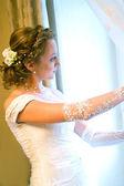 Невеста в свадебном платье против окна — Стоковое фото