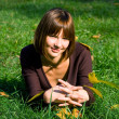Smiling girl on a green grass — Stock Photo