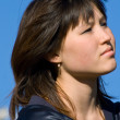 Sad asian girl against blue sky — Stock Photo