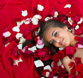 Girl in rose petal — Stock Photo