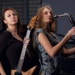 Two young female play on guitar and saxophone — Stock Photo