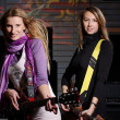Two young females sign the song and play on saxo — Stock Photo