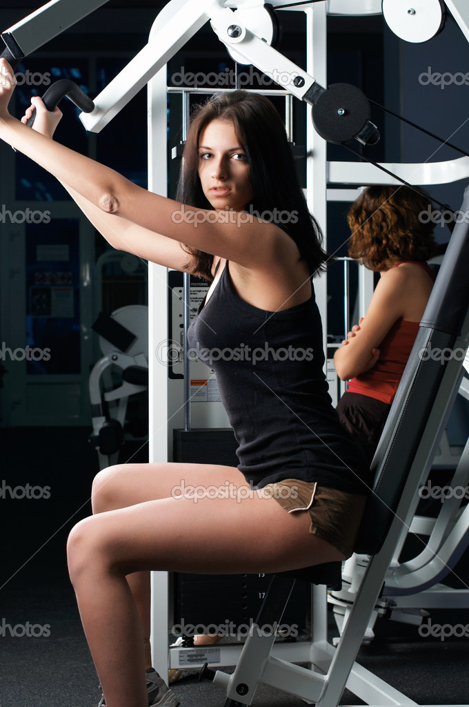 Young charming brunette in a gym on simulators — Stock Photo #2357894