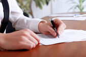Person's hand signing document — Stockfoto