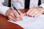 Person's hand signing document — Stock Photo