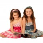 Two beautiful girls reading a magazine — Stock Photo