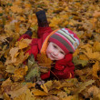 Happy girl lying on autumn leaves — Stock Photo
