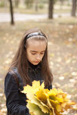 Girl and yellow leaves at autumn — Stockfoto