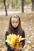 Girl and yellow leaves at autumn — Stock Photo