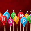 Foto de Stock  : Happy birthday candles on cake