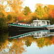 Boats and beautiful autumn forest - Stock Photo