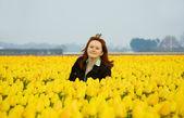 Mulher bonita em tulipas amarelas — Fotografia Stock
