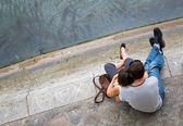 Loving couple sitting on the Seine embankment in Paris, France — Stock Photo
