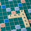 Letters of a board game forming the words Love and Peace — Stock Photo