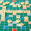 Stock Photo: Letters of board game forming words Financial Crisis