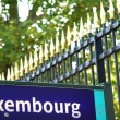 Luxembourg bus stop sign with the Luxembourg Garden grille in the background. Paris, France — Stok fotoğraf