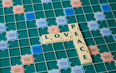 письма в настольную игру, образуя слова любви и мира — Стоковое фото