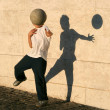 Boy playing catch with his shadow - Stock Photo