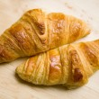 Two croissants on wooden table — Stock Photo