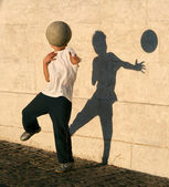 Boy playing catch with his shadow — Stock Photo
