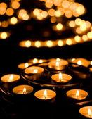 Mnoho hořící svíčky v kostele — Stock fotografie