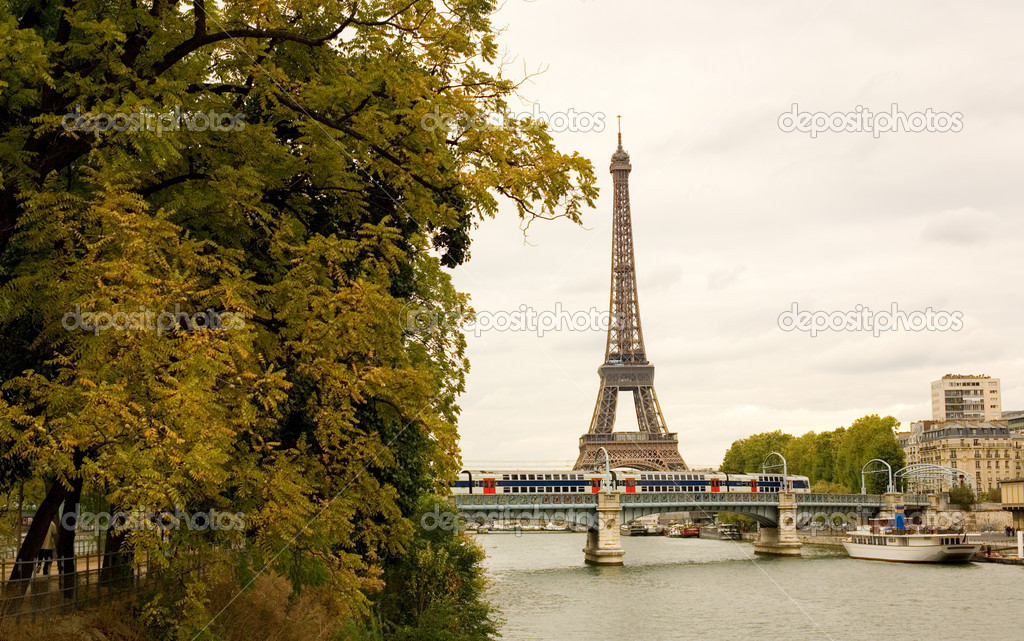 Autumn in Paris. View of the Eiffel tower, moving subway train and autumn trees in sunless day  Stock Photo #1070211