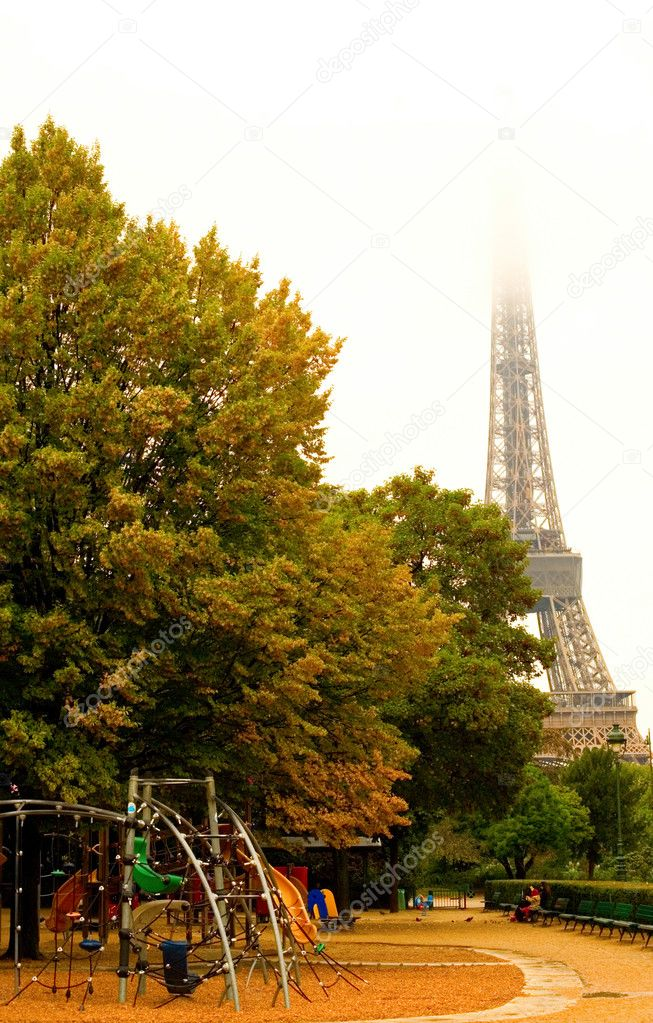 Rainy autumn day in Paris. Deserted playground and misty Eiffel Tower in rainy day — Stockfoto #1077246