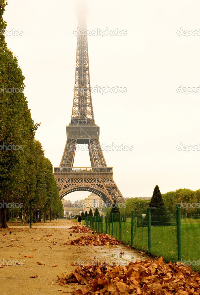 Autumn in Paris. Deserted Field of Mars with heaps of autumn leaves and misty Eiffel Tower in rainy day — Zdjęcie stockowe #1077259