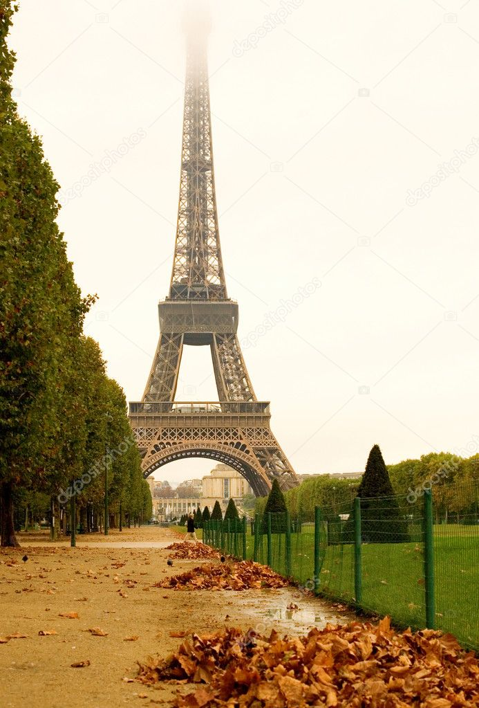 Autumn in Paris. Deserted Field of Mars with heaps of autumn leaves and misty Eiffel Tower in rainy day — Foto Stock #1077259