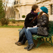 Young couple in love kissing on a bench - Stock Photo