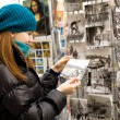 Stock Photo: Beautiful tourist in Paris choosing souvenir pos