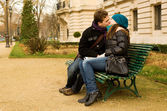 Young couple in love kissing on a bench — Stock Photo