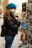 Beautiful tourist in Paris choosing a souvenir p — Stock Photo