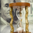 Hourglass on big dollar  background — Stock Photo