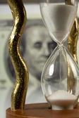 Hourglass on big dollar background — Stock Photo