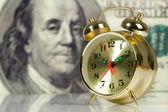 Clock on big dollar background — Stock Photo
