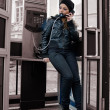 The young girl in telephone booth - Stock Photo